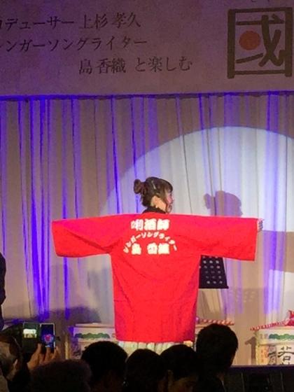 シンガーソングライター「島香織」様のライブステージ衣装として作成させていただきました。 日本酒の「利き酒師」としても名高い彼女のパフォーマンスには法被が良くお似合いですね。背中を向けて貴重なお写真まで頂戴いたしました。 小柄な女性でもこのややオーバーサイズ的なデザインがまた可愛いと思いませんか?