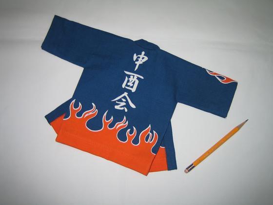 毎年、振る舞い行事を終了した後はせっかく作ったオリジナル法被も処分してしまうそうです。 そこで、何か思い出と記念に残るモノをという事で、こんな素敵なミニチュア法被の作製を頼まれました。実はこの法被、生地も染めも本物と同じ仕様で、袖裏にはオレンジの裏地までちゃんと付いているのです。 縫製には苦労しましたが、これで皆様の思いが成就されるのであれば言う事ありません。  しかし、これカワイイですよね。