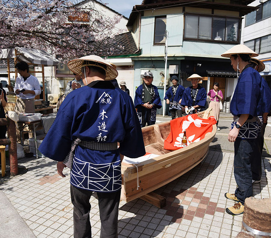 今回素敵な写真をお送りいただいたのは、富山県氷見市にてアートプロジェクトを実行する活動をされている「アートNPOヒミング」様!  今回作成いただいた法被は、木造和船の櫓こぎの方々に着用していただきました。  こちらでは年に数回船を出されているそうですが、今回はお花見シーズンということで、船に乗りながらのお花見遊覧イベントの様子になります。  「今回皆様方のご要望で法被を新調し大好評でした!」との大変ありがたいお言葉を頂けました!